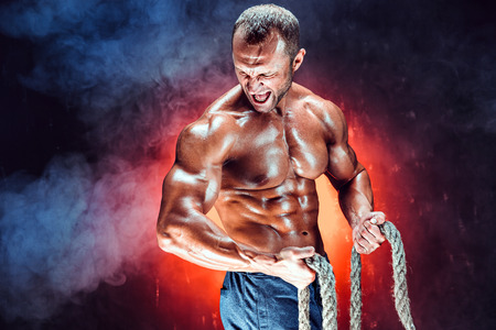 Photo pour Strong shirtless bodybuilder man working out hard with rope. - image libre de droit