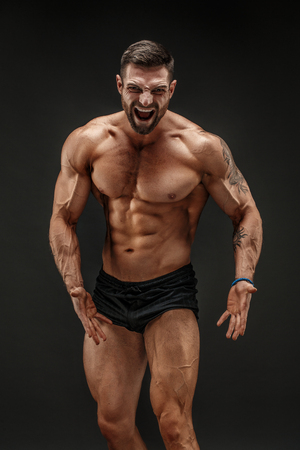 Photo pour Handsome muscular shirtless man screaming and looking at camera isolated on black. - image libre de droit