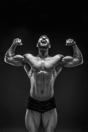 Foto de Handsome muscular shirtless man screaming and looking up isolated on black. - Imagen libre de derechos