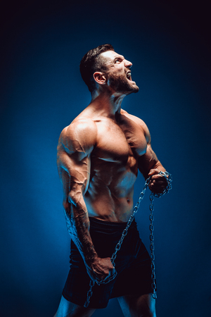 Photo pour Side view of shirtless muscular man screaming and holding chain. - image libre de droit