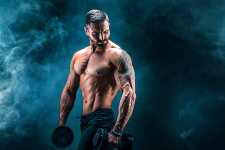 Photo pour Young ripped man bodybuilder with perfect abs, shoulders,biceps, triceps and chest posing with a dumbbell, smoke studio shoot - image libre de droit