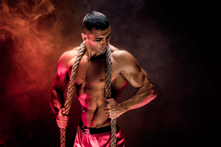 Photo for Strong shirtless bodybuilder man working out hard with rope. - Royalty Free Image