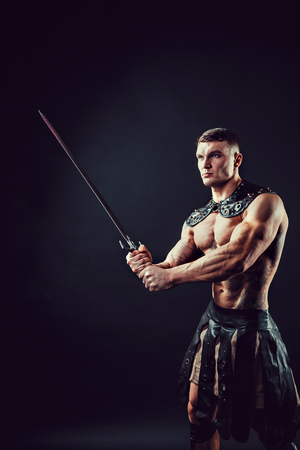 Photo pour Portrait of handsome muscular gladiator with two swords. Studio shot. Black background. - image libre de droit