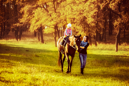Photo pour Little girl riding on a horseback with her mother walking nearby. - image libre de droit