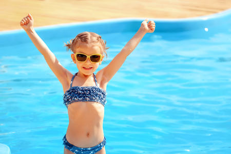 Photo for Summer vacation concept. Little cute girl in sunglasses holding hands up near a swimming pool. - Royalty Free Image