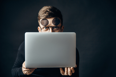 Photo for Young smart man wearing flip-up glasses covering face with laptop looking at camera. - Royalty Free Image