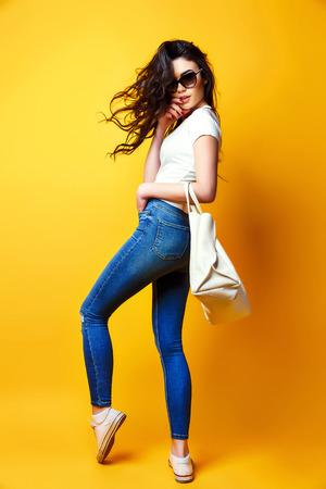 Foto de Beautiful young woman in sunglasses, white shirt, blue jeans posing with bag on the yellow background - Imagen libre de derechos