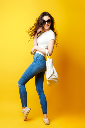 Photo pour Beautiful young woman in sunglasses, white shirt, blue jeans posing with bag on the yellow background - image libre de droit