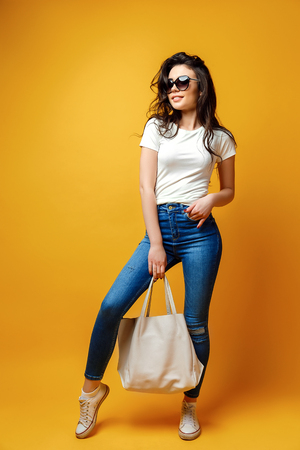 Photo pour Young brunette woman in sunglasses with bag standing on yellow background. - image libre de droit
