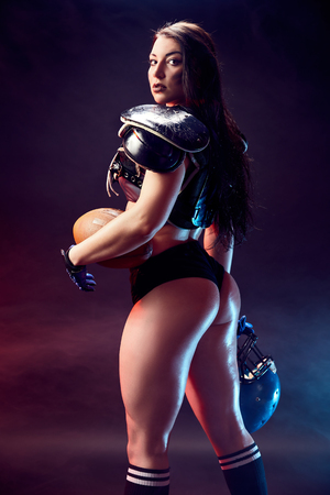 Photo pour Young sportive sexy girl in uniform of rugby football player posing with ball. - image libre de droit
