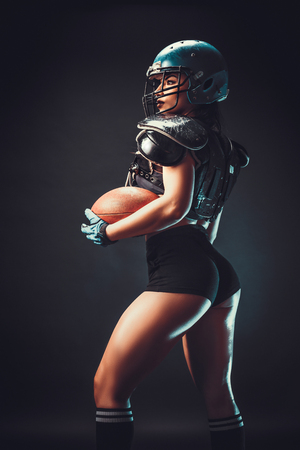 Foto de Sportive serious woman in helmet of rugby player holding ball in stuio on dark background. - Imagen libre de derechos