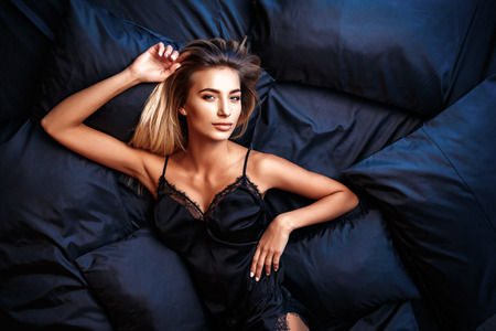 Photo pour fashion photo of sexy glamour woman with blonde hair wearing elegant lace lingerie, lying on black silk bed. top view - image libre de droit