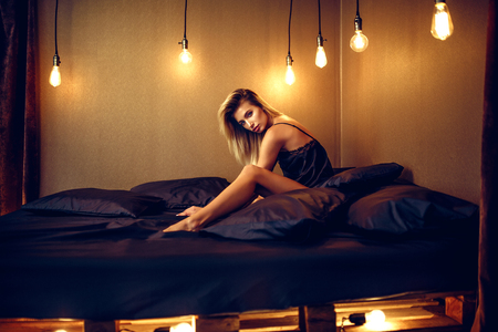 Photo pour fashion photo of sexy glamour woman with blonde hair wearing elegant lace lingerie, lying on black silk bed. - image libre de droit