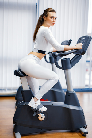 Foto de Indoor cycling woman doing HIT cardio workout biking on indoors gym bike. Girl cyclist working out interval training on bicycle. - Imagen libre de derechos
