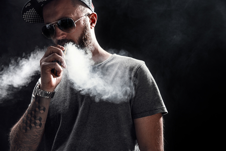 Foto de Pensive Black bearded male dressed in a grey shirt, sunglasses and baseball cap vaping. man in holding a mod. A cloud of vapor. Black background. - Imagen libre de derechos