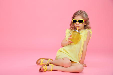 Foto de Pretty little girl in dress and sunglasses sitting on pink with glass jar of cocktail chilling. - Imagen libre de derechos