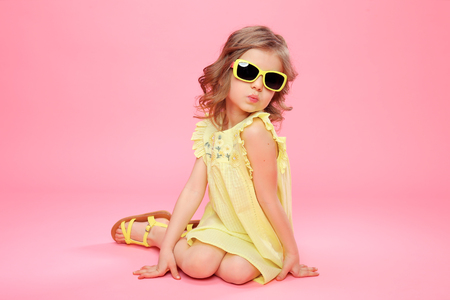 Photo pour Young little girl in yellow dress and sunglasses sitting on pink background in studio. - image libre de droit