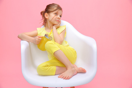 Foto de Charming little girl in yellow sitting in chair and daydreaming holding glass with lemonade and straw on pink background. - Imagen libre de derechos