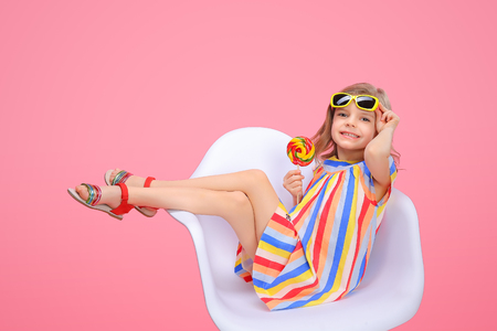 Photo pour Charming trendy little girl in striped dress and sunglasses holding bright lollipop looking at camera smiling on pink background. - image libre de droit