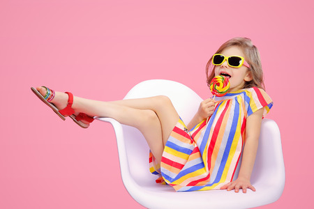 Photo pour Trendy little model wearing multicolored striped dress with sunglasses and licking swirl lollipop. - image libre de droit