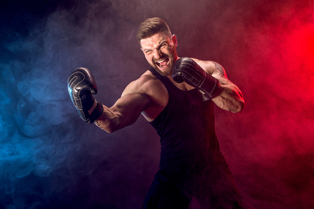 Foto de Sport concept. Sportsman muay thai boxer fighting on black background with smoke. Copy Space. - Imagen libre de derechos