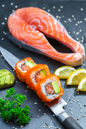 Photo for Sushi served on japanese knife on a black slate plate with a large piece of tuna, salmon - Royalty Free Image