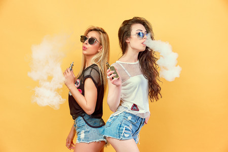 Foto de Side view of trendy young female in glasses and shorts standing and smoking on studio background - Imagen libre de derechos