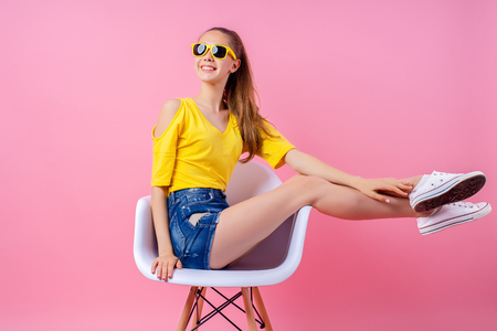 Photo pour Smiling teenage female in sunglasses sitting in white chair in studio with legs raised on pink background - image libre de droit