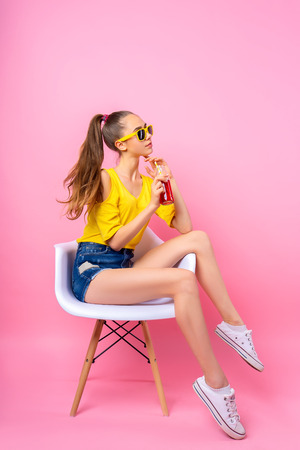 Photo for Adorable girl in sunglasses sitting in chair in studio holding bottle and drinking beverage through straw on pink background - Royalty Free Image
