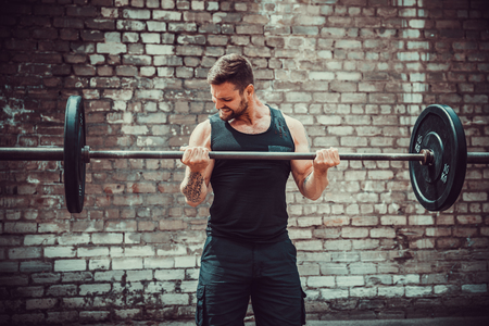 Foto de Athletic man working out with a barbell in front of brick wall. Strength and motivation. Outdoor workout. Biceps exercise. - Imagen libre de derechos