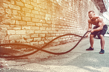 Photo for Athletic man working out with rope in front of brick wall. Strength and motivation. Outdoor workout. - Royalty Free Image