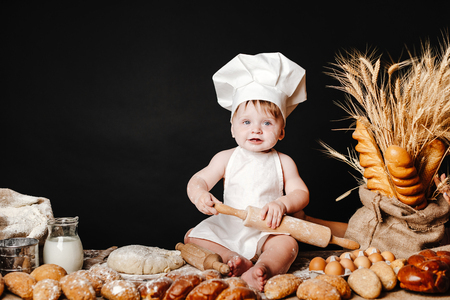 Photo pour Charming toddler baby in hat of cook and apron sitting on table with bread loaves and cooking ingredients laughing happily - image libre de droit