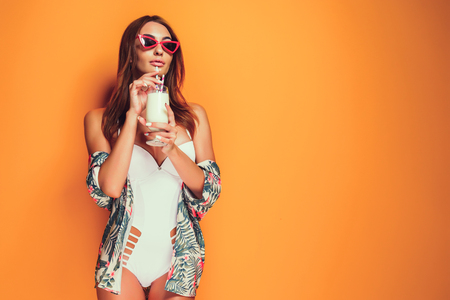 Photo pour Lovely young female in swimwear and sunglasses holding glass of fresh drink while standing on yellow, orange hot background. Copyspase - image libre de droit