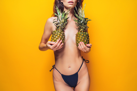 Foto de Anonymous young female in black panties holding ripe pineapples near boobies while standing on bright yellow background - Imagen libre de derechos