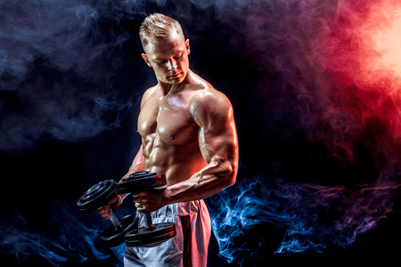 Photo pour Topless man exercising biceps with dumbbells posing in studio full of colored smoke - image libre de droit