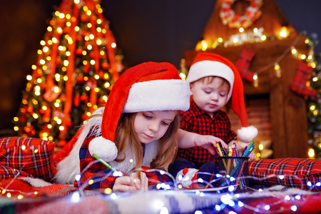 Foto de Charming girl in Santa hat lying on the floor and writes letter, draws with pencil and her little brother who interferes with her, plays with pencils in warm room with garlands, lights - Imagen libre de derechos