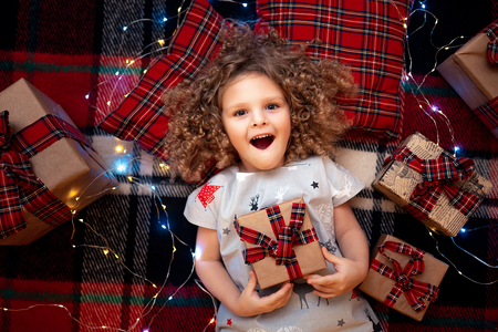 Foto de Closeup portrait of smiling cute little child in holiday christmas pajamas holding gift box. Top view of happy kid laying on checkered plaid near presents. - Imagen libre de derechos