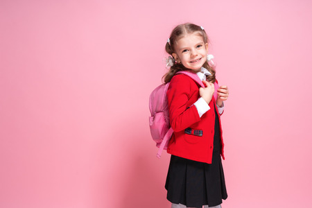 Photo pour Back to school. Child with schoolbag. Schoolgirl 7-8 years old in a red jacket, white shirt, pigtails, black sarfan, school uniform with school bag isolated on pink - image libre de droit