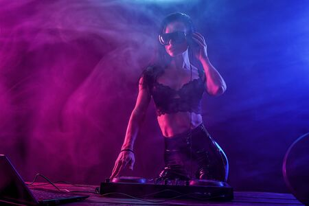 Photo for Young sexy woman dj in bra and sunglasses playing music. Headphones and dj mixer on table. Colorful Smoke on background - Royalty Free Image