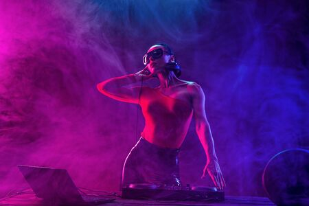 Photo for Young sexy woman dj playing music. Headphones and dj mixer on table. Colorful Smoke on background - Royalty Free Image