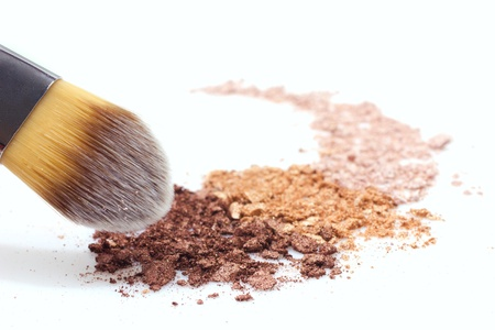 makeup brush and multicolored eyeshadow on white background