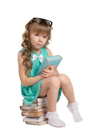 Photo for little beautiful girl with long curls, in big optical glass sit on pile of old books holding  book and  look at camera isolated on white - Royalty Free Image