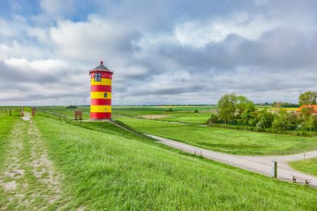 Photo pour The Pilsum lighthouse on the North Sea coast of Germany. - image libre de droit
