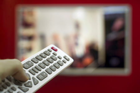 Foto de The remote in the hand switch channels on the TV hanging on the red wall. - Imagen libre de derechos