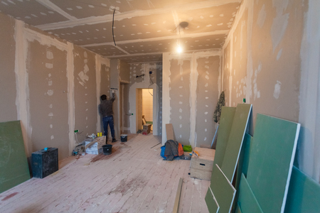 Photo pour Worker prepares walls for remodeling it by drywall (plasteboard, gypsum) and  interior of apartment with materials during on the renovation and construction. - image libre de droit