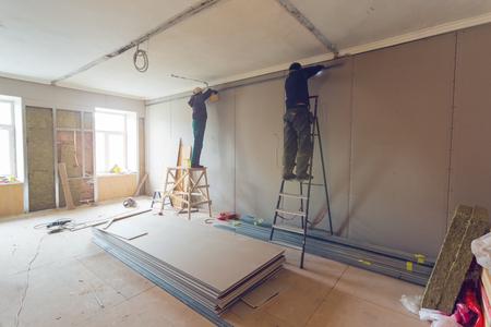 Foto de Workers are installing plasterboard (drywall) for gypsum walls in apartment is under construction, remodeling, renovation, extension, restoration and reconstruction. - Imagen libre de derechos