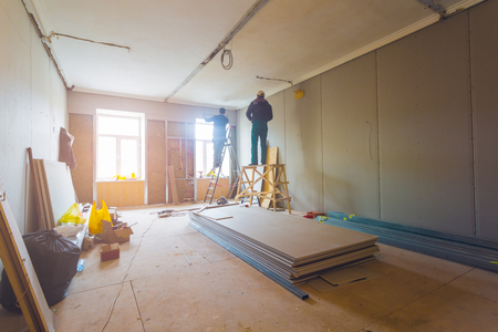 Foto de Working process of installing metal frames for plasterboard (drywall) for making gypsum walls with ladder and tools in apartment is under construction, remodeling, renovation, extension, restoration and reconstruction - Imagen libre de derechos