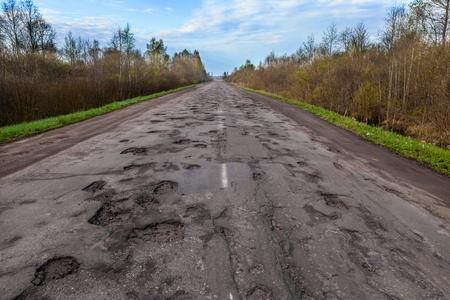 Photo pour Dangerous potholes in the asphalt rural road. Road damage - image libre de droit