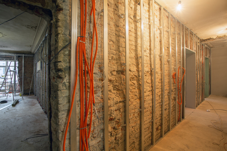 Photo pour Working process of install of frames for plasterboard and corrugated pipe with electrical cables in an apartment is under construction, overhaul, remodeling, rebuilding, home improvements, reconstruction  and renovation. - image libre de droit