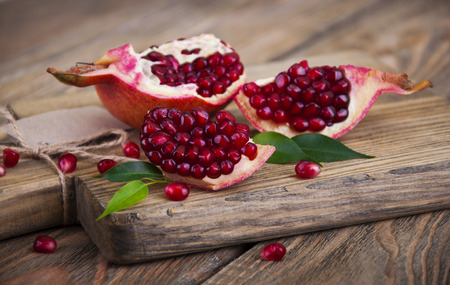 Photo for Juicy pomegranate and red grains on wooden background - Royalty Free Image